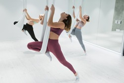 group of young sportive women stretching on aerial yoga hammocks in gym