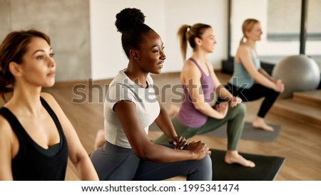 Group of young sportswomen warming up on sports training at health club. Focus is on happy African American woman.  Foto stock ©