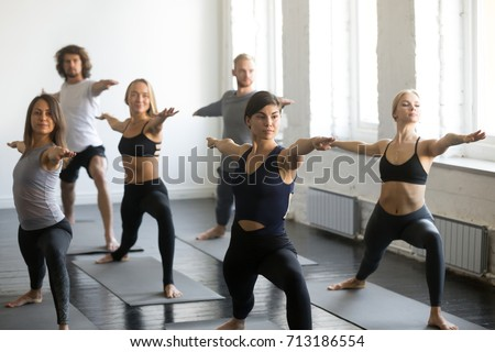 Group of young sporty attractive people practicing yoga lesson with instructor, standing in Warrior Two exercise, Virabhadrasana pose, working out, indoor, studio. Wellbeing, wellness concept  #713186554