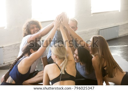 Group of young sporty people celebrating giving friends a high five. Assemble the team building, encouraging members to work well together, raised hands, gesture of greeting, good-fellowship triumph