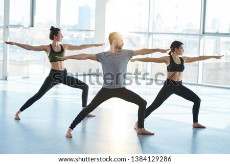 Group of young sporty people in activewear standingon the floor in one of yoga positions with their arms outstretched #1384129286