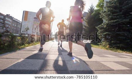 group of young sporty people jogging at sunny morning in the city