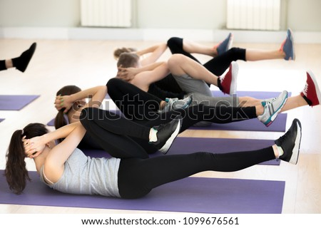 Group of young sporty people practicing in sport gym, doing crisscross pose, bicycle crunches exercise, indoor full length, active students working out in fitness club, studio. Wellness concept