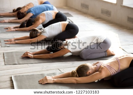 Group of young sporty people practicing yoga, doing Child exercise, Balasana pose, working out, indoor full length, mixed race female students training at club or studio. Well being, wellness concept ストックフォト ©
