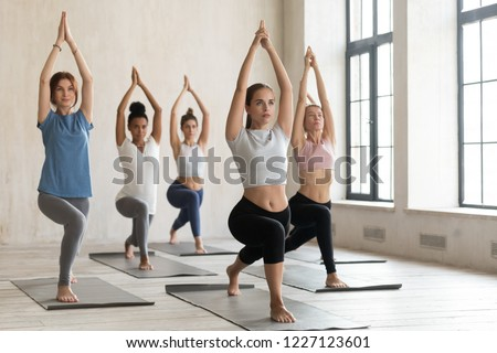 Group of young sporty people practicing yoga lesson, doing Warrior one pose, Virabhadrasana 1 exercise, working out, indoor full length, mixed race students training at sport club or yoga studio