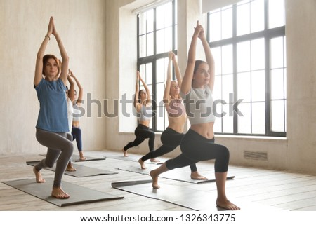 Group of young sporty people practicing yoga lesson, doing Warrior one pose, Virabhadrasana I exercise, working out, indoor full length, mixed race students training at sport club or studio