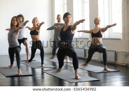 Group of young sporty people practicing yoga lesson, doing Warrior Two exercise, Virabhadrasana 2 pose, working out, indoor full length, students training in club, studio #1065436982