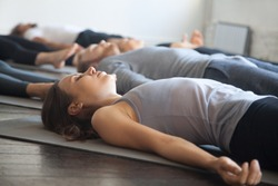 Group of young sporty people practicing yoga lesson with instructor in gym, lying in Dead Body exercise, doing Savasana, Corpse pose, friends relaxing after working out in sport club, studio image