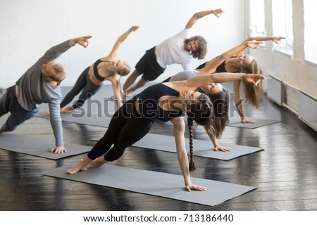 Group of young sporty people practicing yoga lesson with instructor, stretching in Bending Side Plank exercise, Vasisthasana pose, working out, indoor studio image. Wellbeing, wellness concept