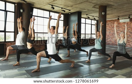 Group of young sporty people practicing yoga, standing in Warrior one pose, Virabhadrasana I pose, working out in loft studio. #1278061699