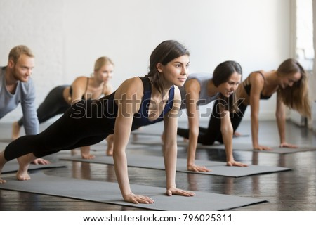 Group of young sporty people practicing yoga with instructor, doing Plank exercise, Push ups, press ups pose, working out indoor, students training in club, studio. Wellbeing, weight loss concept