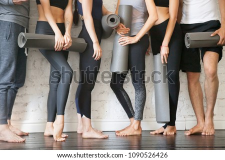 Group of young sporty people with fitness yoga exercise mats standing beside white wall. Rest from fitness activity, time to recover strength. Sport instructors inviting for class. Close up view photo