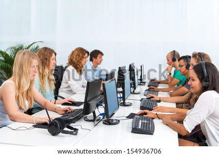 Group of young students doing training course on computers.