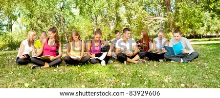 group of young students sitting i park and learning