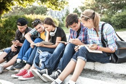 group of young students with books and gadgets sit on the steps in the park