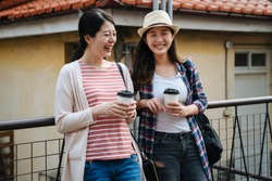 Group of young stylish happy people leaning against railing and talking while drinks coffee in paper cup standing outdoor in small town with red brick roof of old historic house. two girls laughing