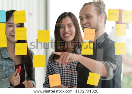 Group of young successful creative multiethnic team smile and brainstorm on project together in modern office with post note or sticky note. Caucasian man point on glass wall sharing idea.
