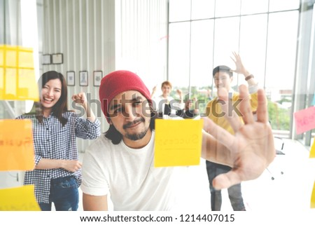 Group of young successful creative multiethnic team smiling and brainstorm together in meeting. Happy hispster asian man looking at sticky post note on glass wall sharing idea with engaged cheerful.