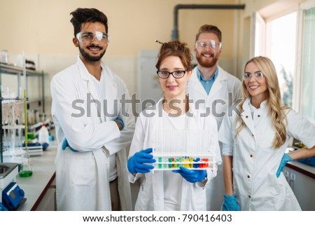 Group of young successful scientists posing for camera