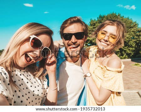Group of young three stylish friends in the street.Man and two cute girls dressed in casual summer clothes.Smiling models having fun in sunglasses.Women and guy making photo Pov selfie on smartphone