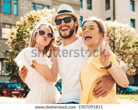 Group of young three stylish friends posing in the street. Fashion man and two cute female dressed in casual summer clothes. Smiling models having fun in sunglasses.Cheerful women and guy going crazy Stock foto ©