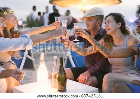 Group of young tourist friends cheering with champagne at beach kiosk party - Happy people having fun in summer holidays - Focus on girls hands glasses - Fun,vacation, hanging out and youth concept