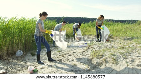 Group of young volunteers helping to keep nature clean and picking up the garbage from a sandy shore. - Shutterstock ID 1145680577