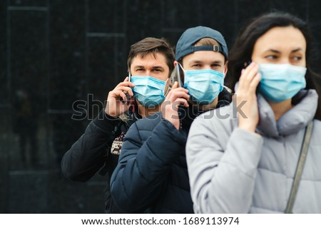 Group of young volunteers wearing face masks with mobile phones. Volunteers are ready to help. Call to volunteers. The concept of mutual assistance and support. World coronavirus pandemic.