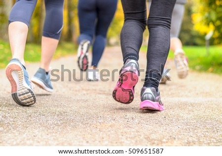 Group of young woman jogging together in a park with a close up low angle view from behind of their lower legs and running shoes