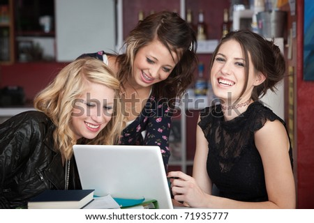 Group of young women having a good time while sitting around a laptop