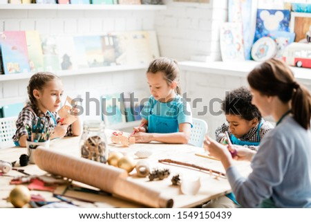 Group of youthful and clever schoolkids and their teacher sitting by table and making paper decorations for forthcoming holiday Сток-фото ©