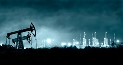 Group oil rigs and brightly lit industrial site at night. Toned.