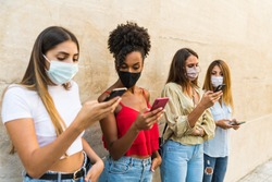 Group only young women multiracial with face mask using smartphone - Group only young girls interracial face mask using smartphone - Group only young female multiethnic face mask using smartphone