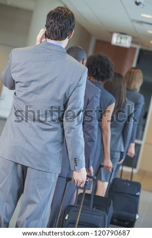 Group or team of men and women, businessmen & businesswomen talking on cell phone and traveling in line through an airport with rolling suitcases