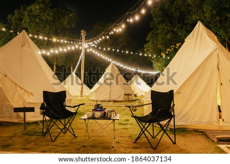 Group outdoor camping teepee tent and night light with two empty chairs with picnic table and accessories in the forest. Glamping camping tent in the forest under night sky.