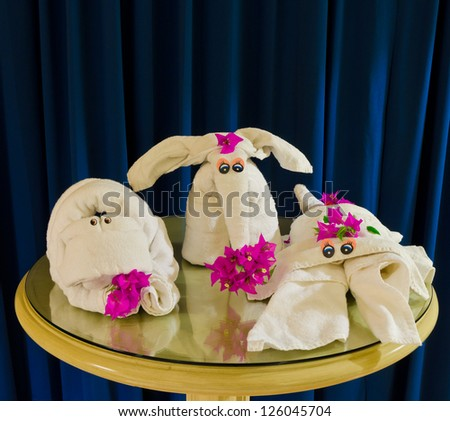 Group, pack of  animals made from white spa towels twisted ( has been folded out of a towel )  in the different forms form such as  a abstract creature, elephant and scorpion. Decorated with flowers.