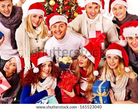 Group people and  Santa holding gift box near  Christmas tree.
