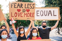 Group people during a peaceful demonstration on human rights, against racism and for social equality  - Millennials holding signs in hand with lettering and drawings with face mask for Coronavirus