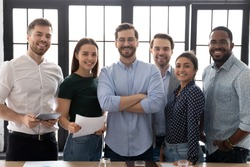 Group picture of happy diverse multiethnic young businesspeople posing together at workplace in office, portrait of smiling multiracial colleagues coworkers show unity and motivation in business