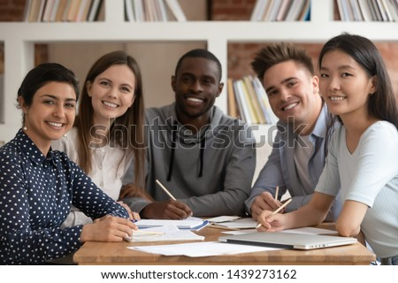 Group picture of happy multiethnic young people sit at shared desk look at camera studying together, multicultural excited students or groupmates smiling posing for photo working in library