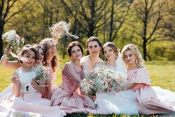 Group portrait of bride and bridesmaids. Wedding. Bride in wedding dress and bridesmaids in pink dresses at wedding day. Stylish wedding in pink color. Marriage concept.