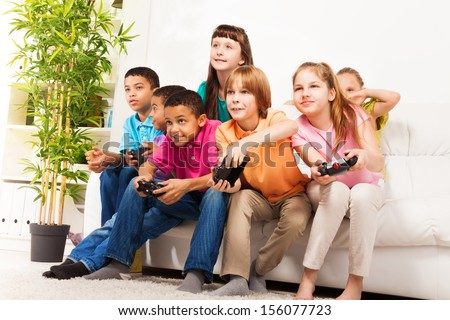 Group portrait of diversity looking children boys and girls, friends, playing videogame sitting on the couch in living room with intense expression on their faces, holding game controller