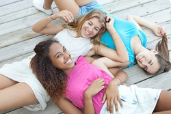 Group portrait of ethnically diverse adolescent girls friends laying together on a wooden deck, laughing smiling joyfully looking at camera, relaxing outdoors. Recreation travel lifestyle, teenagers.
