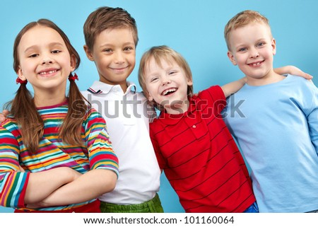 Group portrait of four smiling friends hugging