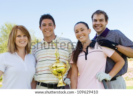 Group portrait of friends holding winning trophy at golf course