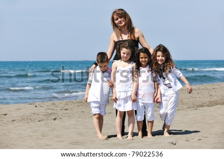 group portrait of happy childrens with young female  teacher on beach - stock photo