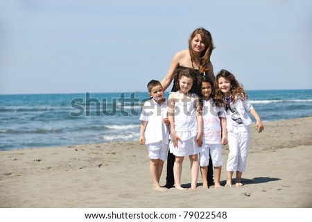group portrait of happy childrens with young female  teacher on beach