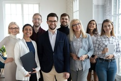 Group portrait of happy diverse colleagues of different ages. United businesspeople of 30s and 50s looking at camera. Team of trainee interns and coaches posing together in office. Teamwork concept