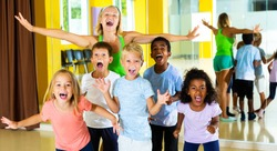 Group portrait of happy young tweenagers with female choreographer in modern dance studio