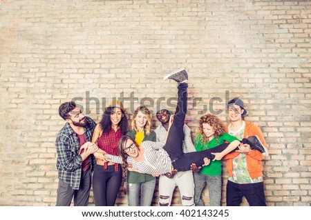 Shutterstock Group portrait of multi-ethnic boys and girls with colorful fashionable clothes holding friend and posing on a brick wall - Urban style people having fun - Concepts about youth  and togetherness
